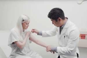 Brian S. Kim, MD, examining eczema patient